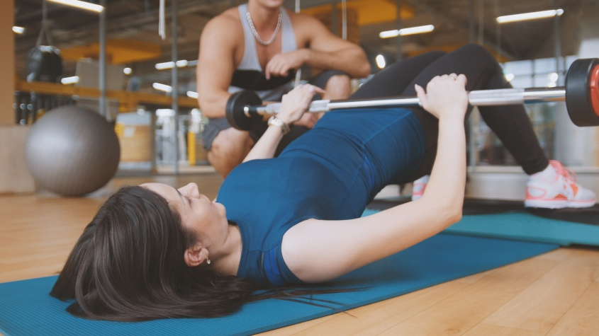 Young attractive brunette women doing exercise for buttocks - the rise of a body lying over the bar